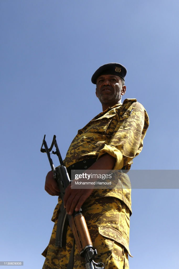 A Houthi fighter stands guards as Yemeni mourners carry coffins of