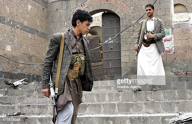 Houthi fighters inspect the site of a car bomb attack near of Qubbat alMahdi Mosque on June 20 2015 in Sanaa Yemen At least three people were killed...