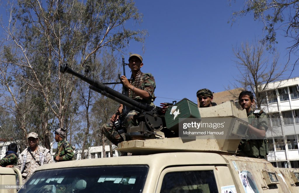 Houthi fighters ride a truck as they stand guard during a gathering