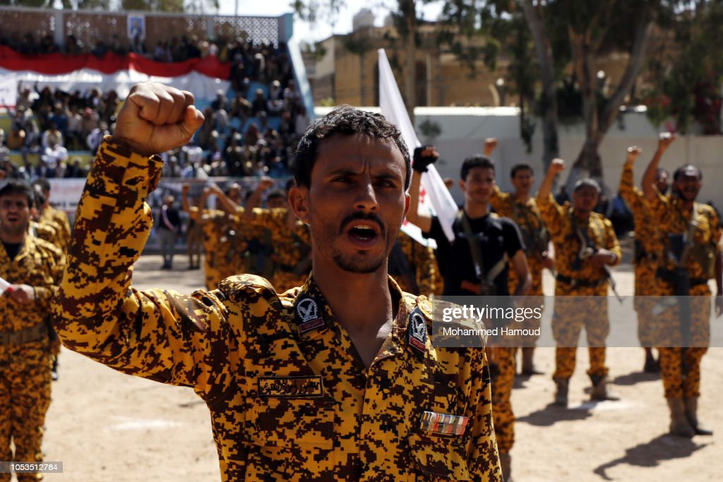 Houthi fighters shout slogans while they participate in a gathering