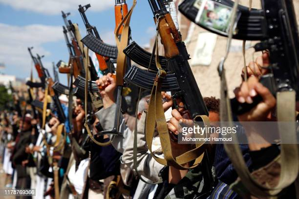 Houthi followers hold their guns during a tribal gathering against the continued war and blockade on October 03, 2019 in Sana'a, Yemen.