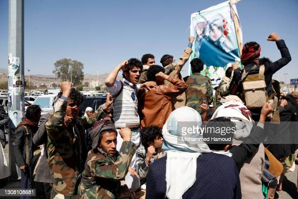 Houthi followers ride vehicles that carry coffins of their fighters killed in ongoing fighting between the Houthis and forces of the government over...
