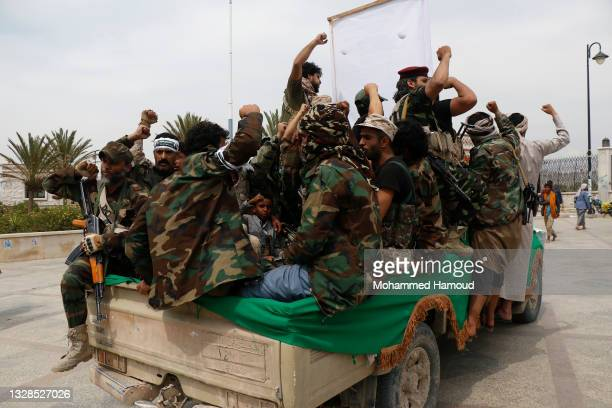 Houthi followers shout slogans as they ride a truck carrying the coffin of a fighter who was killed in the recently intensified fighting in Al-Bayda...