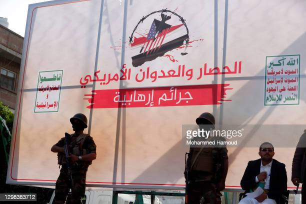 Houthi soldiers stand in front of a banner with words read in Arabic during a protest against the decision by the Trump administration to designate...