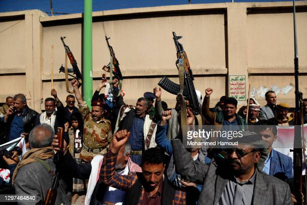 Houthi supporters raise their rifles as they chant slogans during a protest staged against the decision of the former U.S. President's administration...