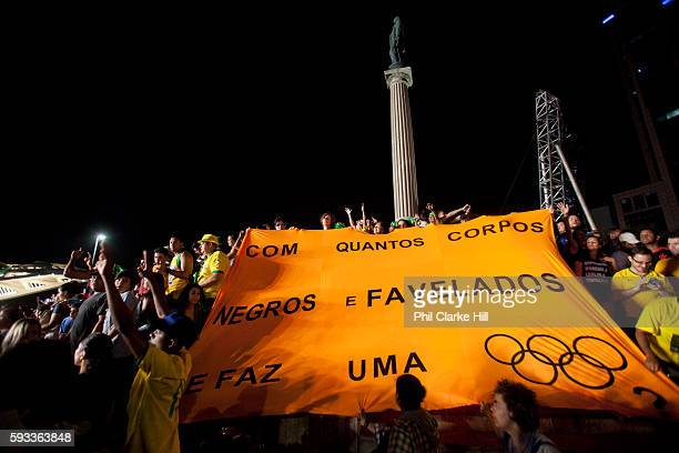 'How many black and favela people's bodies does it take to make an Olympics' banner protest at the BrazilGermany football match live site Praca Maua...
