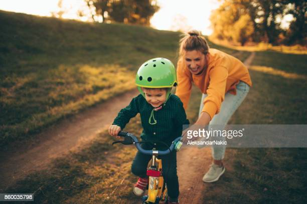 how to ride a bike? - mother and son stock photos and pictures
