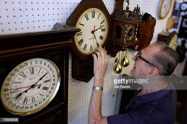 Howard Brown adjusts the time on a clock he just repaired as he hangs it on the wall at Browns Old Time Clock Shop March 6 2007 in Plantation Florida...