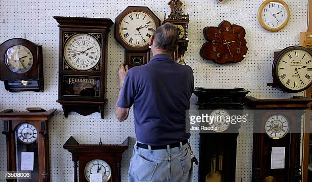 Howard Brown hangs a clock he just repaired on the wall at Browns Old Time Clock Shop March 6 2007 in Plantation Florida This year day light savings...