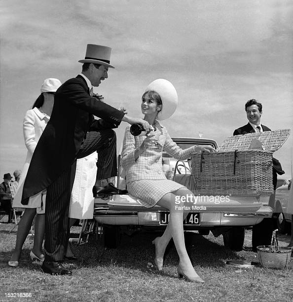 Howard D Kiel of Toorak pours a glass of champagne for English model Jean Shrimpton as she sits on the tailboard of a station wagon [ute] in the car...