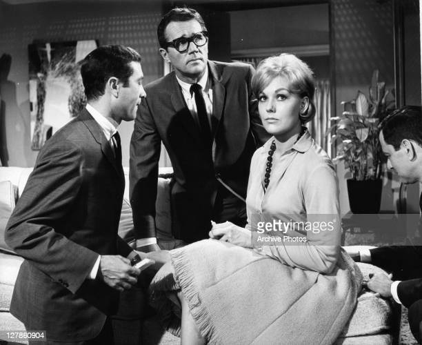 Howard Duff looking up Kim Novak sits with Tony Randall sitting behind her in a scene from the film 'Boys' Night Out' 1962