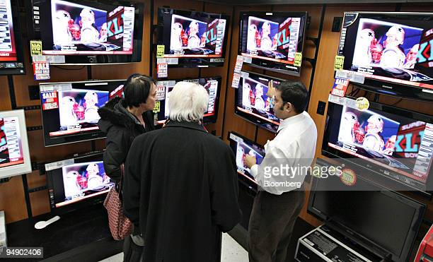Howard Greenwald center and his wife Louise talk to an employee about flatscreen televisions inside a PC Richard Sons store in New York US on...