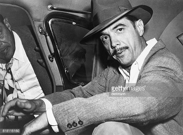 Howard Hughes seated in an automobile.