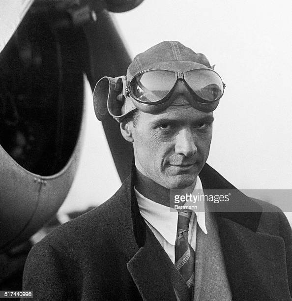 Howard Hughes standing in front of an airplane in a leather flight helmet and goggles.