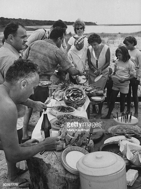 Howard Johnson VP Pierre Franey White House cook Rene Verdon and Caravelle chef Roger Fessageut preparing their dishes on the beach at the chefs...