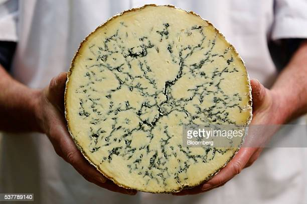 Howard Lucas production manager at Cropwell Bishop Creamery Ltd poses for a photograph with a cut Stilton cheese in Cropwell Bishop UK on Monday...