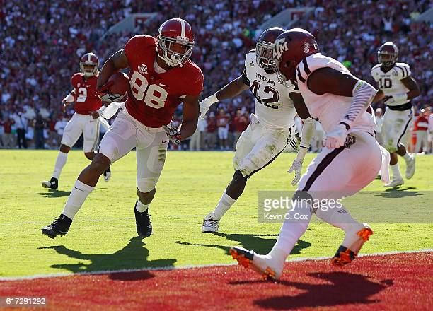 J Howard of the Alabama Crimson Tide scores a touchdown against Otaro Alaka and Donovan Wilson of the Texas AM Aggies at BryantDenny Stadium on...