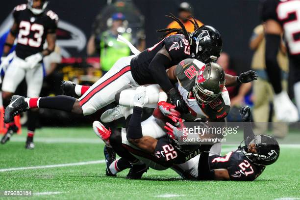 J Howard of the Tampa Bay Buccaneers is tackled by Damontae Kazee Keanu Neal and De'Vondre Campbell of the Atlanta Falcons during the second half at...