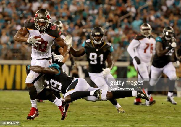 J Howard of the Tampa Bay Buccaneers is tackled by Tashaun Gipson of the Jacksonville Jaguars during a preseason game at EverBank Field on August 17...