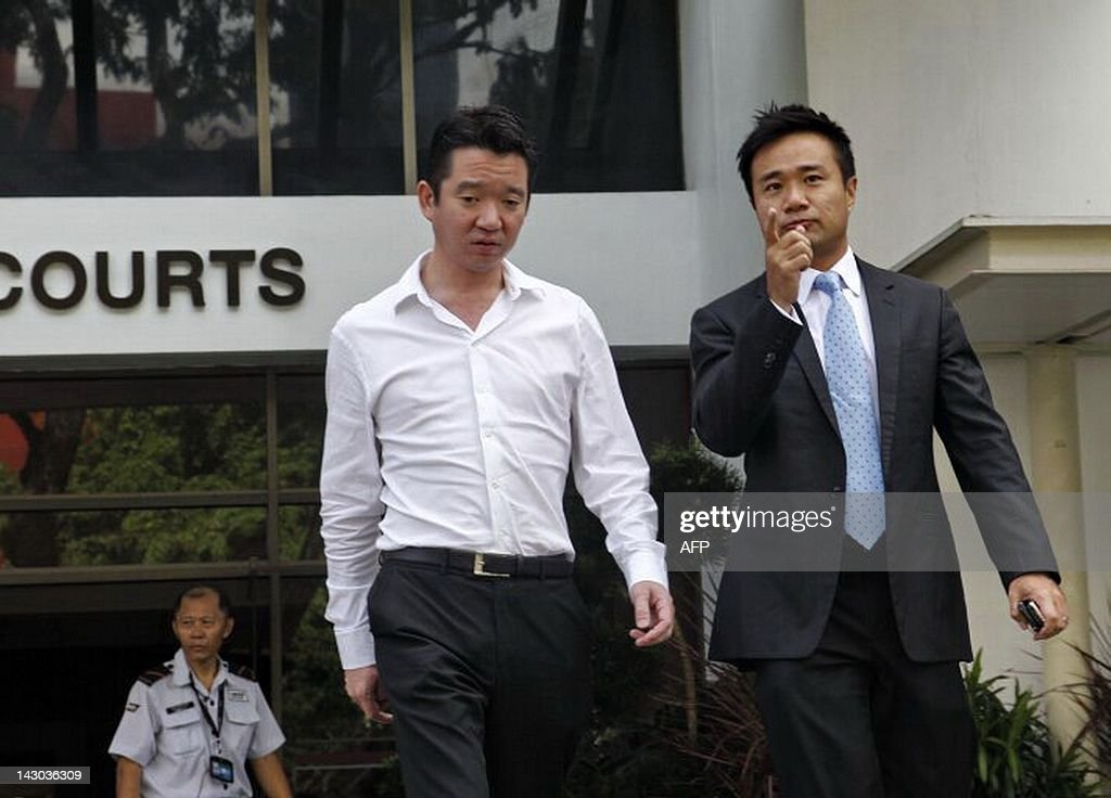 Howard Shaw (L in white shirt), a member of a prominent Singaporean family, is photographed on April 18, 2012 leaving a courthouse where he was formally charged with having paid sex with a prostitute under 18 years old, an offence in Singapore. The scandal over the underage Singaporean callgirl widened after Shaw and a Swiss former banker were included among 48 men charged in the case.