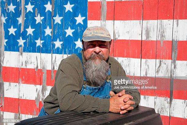 Howard The Teacher Poses In Front Of Us Flag On His Shed, Near Augusta, Maine.