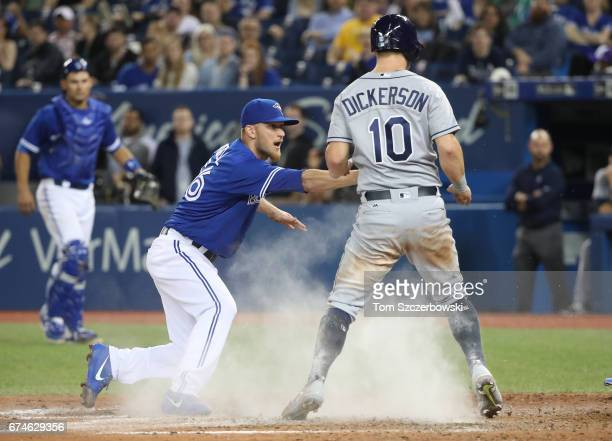 P Howell of the Toronto Blue Jays applies a late tago on Corey Dickerson of the Tampa Bay Rays as Dickerson scores a run on a wild pitch in the ninth...