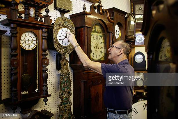 Howie Brown adjusts the time on a clock back one hour for the end of day light savings time at Brown's Old Time Clock Shop November 2 2007 in...