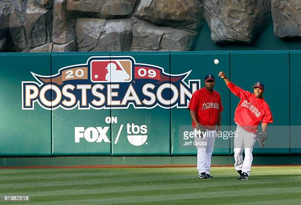 Howie Kendrick and Chone Figgins of the Los Angeles Angels of Anaheim shag balls in the outfield during an offday workout part of the ALCS during the...