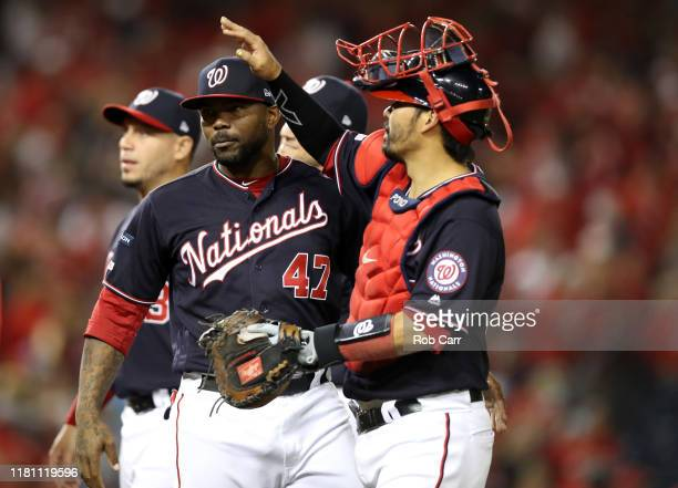 Howie Kendrick and catcher Kurt Suzuki of the Washington Nationals celebrate defeating the St Louis Cardinals 81 after game three of the National...