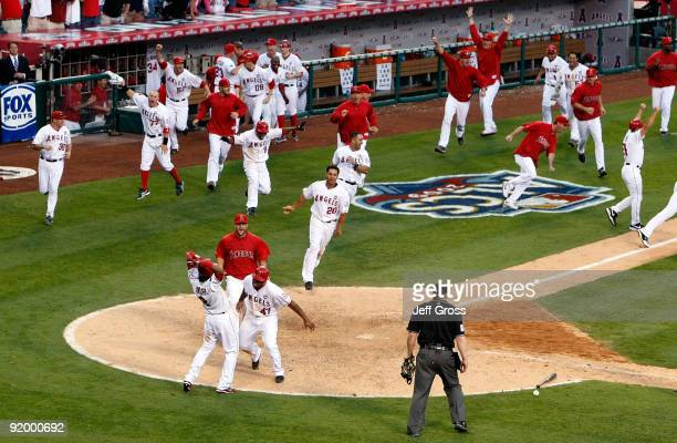 Howie Kendrick of the Los Angeles Angels of Anaheim celebrates with teammate Erick Aybar after sliding home off of Jeff Mathis walk off double in...