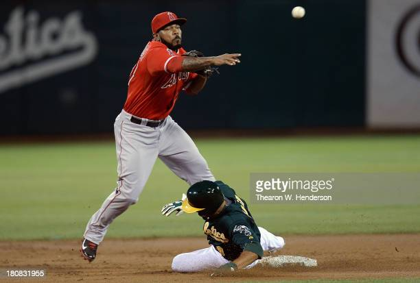 Howie Kendrick of the Los Angeles Angels of Anaheim gets his throw off over the sliding Coco Crisp of the Oakland Athletics but not in time to...