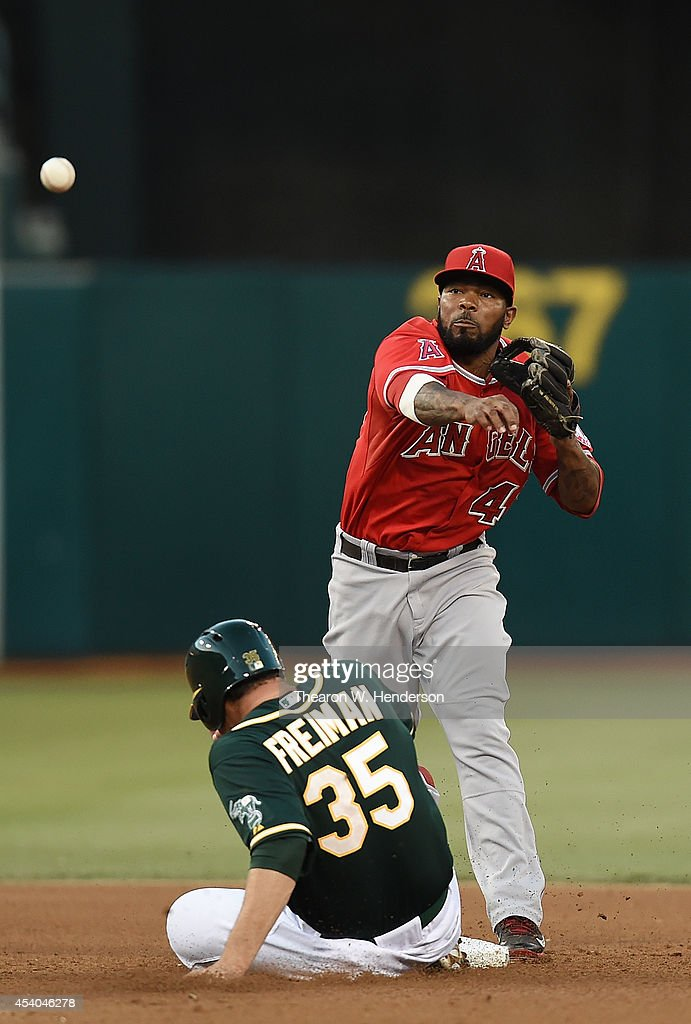 Howie Kendrick #47 of the Los Angeles Angels of Anaheim to complete the double-play throws over the top of Nate Freiman #35 of the Oakland Athletics in the bottom of the fourth inning at O.co Coliseum on August 23, 2014 in Oakland, California.
