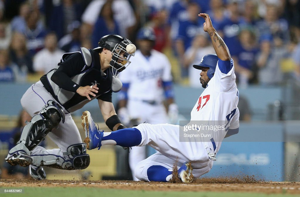 Howie Kendrick #47 of the Los Angeles Dodgers slides home to score on a sacrifice fly by Adrian Gonzalez in the seventh inning as the ball gets away from catcher Tony Wolters #14 of the Colorado Rockies at Dodger Stadium on July 2, 2016 in Los Angeles, California.