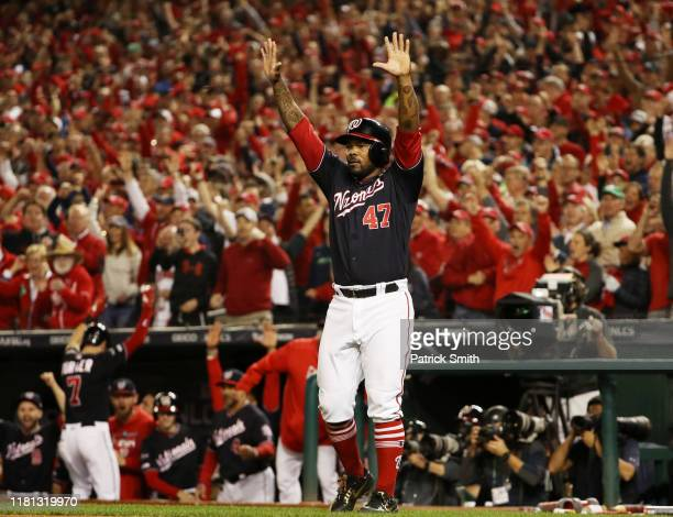 Howie Kendrick of the Washington Nationals celebrates a run by Ryan Zimmerman in the first inning against the St Louis Cardinals during game four of...