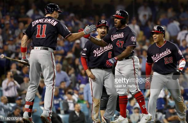 Howie Kendrick of the Washington Nationals celebrates after hitting a grand slam with teammates Juan Soto Ryan Zimmerman and Anthony Rendon in the...