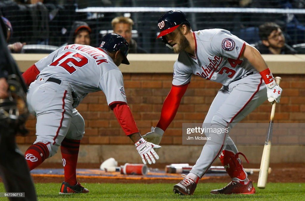 Howie Kendrick #12 of the Washington Nationals celebrates his ninth inning home run against the New York Mets with teammate Bryce Harper #34 at Citi Field on April 16, 2018 in the Flushing neighborhood of the Queens borough of New York City.