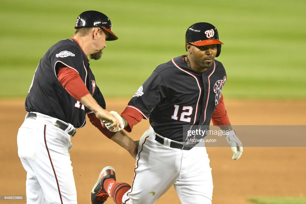 Howie Kendrick #12 of the Washington Nationals celebrities a solo home run in the fifth inning with third base coach Bob Henley #13 during a baseball game against the Colorado Rockies at Nationals Park on April 12, 2018 in Washington, DC.