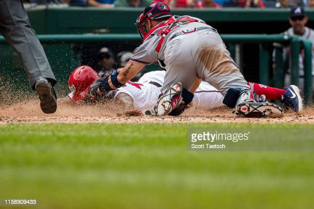 Howie Kendrick of the Washington Nationals is tagged out at home plate by Tyler Flowers of the Atlanta Braves during the sixth inning at Nationals...
