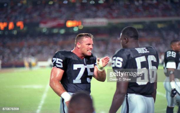 Howie Long confers with Aundray Bruce in a game against the Los Angeles Rams at Anaheim Stadium circa 1994 in AnaheimCalifornia