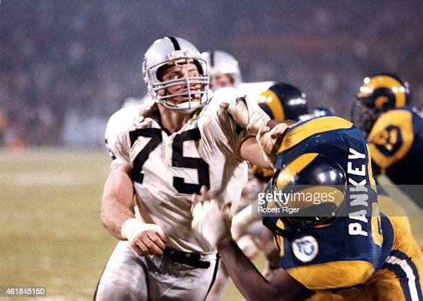 Howie Long of the Los Angeles Raiders battles with Irv Pankey of the Los Angeles Rams on December 23 1985 at Anaheim Stadium in Anaheim California