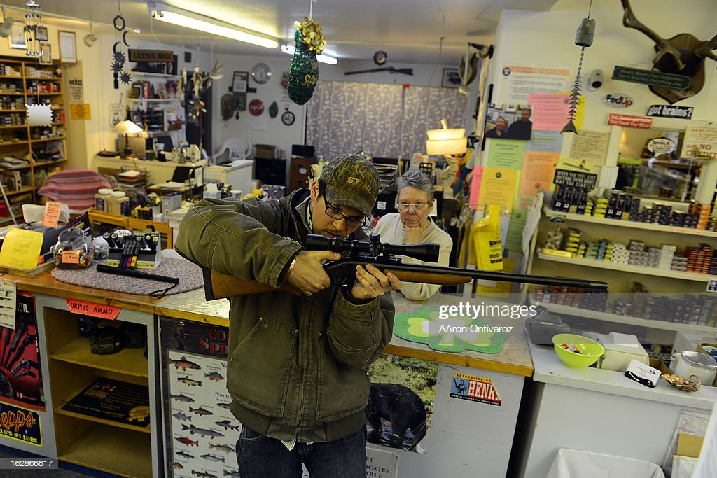 Howllowpoint Gun Shop Owner Erin Jerant looks on as Justin Noga checks the scope mount in Walsenburg. Jerant says she has known Noga since he was young enough to sit on the store's countertops. Gun owners in southern Colorado largely agree that responsible ownership begins at home.
