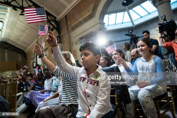 Hoyannee Malatchanyan a 10 yearold from Armenia waves the American flag after taking the Oath of Allegiance to become a US citizen during a...