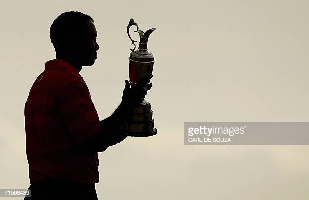 Tiger Woods of the United States poses the Claret Jug after winning the 135th British Open Golf Championships in Hoylake in Liverpool in northwest...