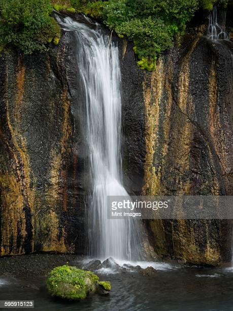 Hraunfossar waterfalls, a cascade of water over a sheer cliff into a pool.