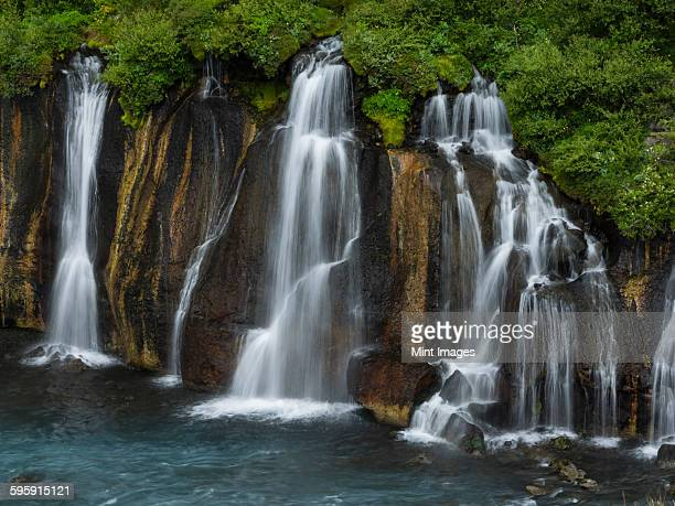 Hraunfossar waterfalls, a series of cascading torrents flowing from lava fields over a sheer cliff into the river Hvita.
