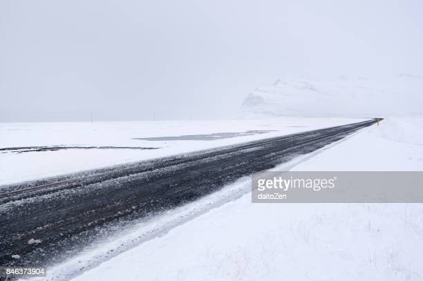 Hringvegur Ring Road in Iceland covered by ice and snow leading through winter landscape near Höfn, Southeast Iceland, Europe