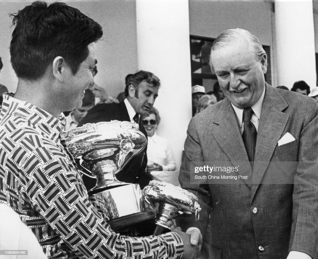 Hsieh Min-nan (left) receives the trophy from Sir Douglas Clague (right) after winning the Hongkong Open Golf Championship in Fanling. 27FEB77 : News Photo