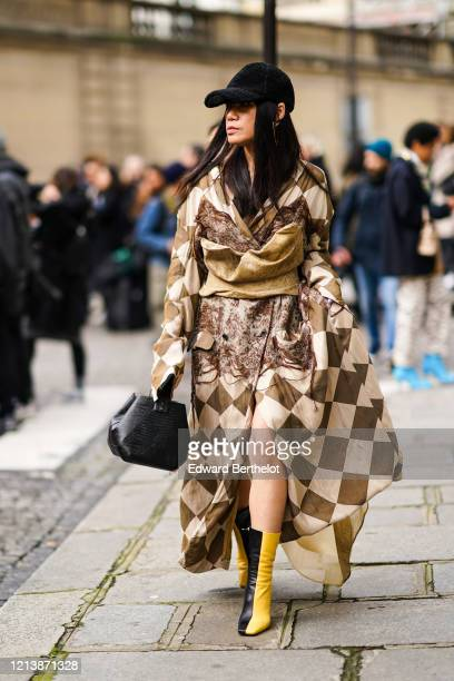 Hsinwei Ho wears a black cap, a brown and white checked pattern dress, a black leather bag, yellow and black leather boots, outside Altuz, during...