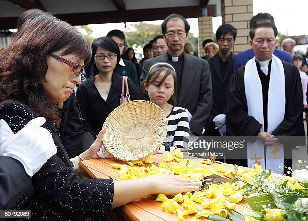 Hsiu Chuan Chen the mother of Tom Hsu scatters flower petals over her son's coffin after his funeral at Elim Christian College on April 21 2008 in...