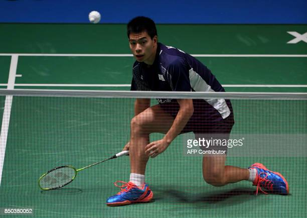Hsu Jenhao of Taiwan hits a return against HS Prannoy of India during their men's singles second round match at the Japan Open Badminton...